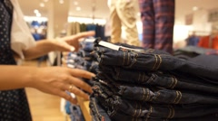 Woman Shopping for Jeans in Store - stock footage