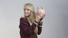 Beautiful Blonde Holding Piggy Bank - Savings and Investment Stock Footage