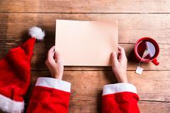 Santa Claus and wishlist - stock photo