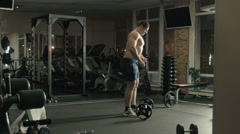 The man the weightlifter lifts a bar in a gym - stock footage