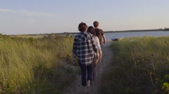 Group Of Teens Walk Down Sandy Path Toward Water Stock Footage