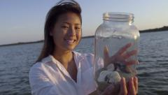 Asian Teen Holds Up Memory Jar Of Sand And Shells From Her Beach Vacation - stock footage