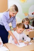 Teacher helps little girl with the task - stock photo
