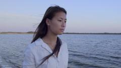 Portrait Of Asian Teen Girl Walking Along Shoreline At Sunset - stock footage