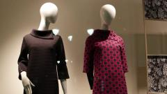 Faceless two dummies mannequins in dresses are in storefront a clothing store - stock footage