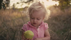 A cute little girl in a field holding an apple that she just picked Stock Footage