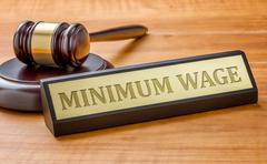 A gavel and a name plate with the engraving Minimum Wage Stock Photos