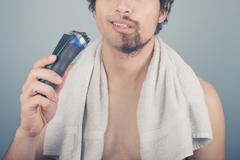 Man with broken razor cannot finish shaving - stock photo