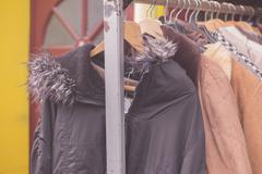 Winter jackets hanging on rail outside - stock photo