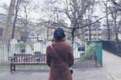 Woman walking around a graveyard - stock photo