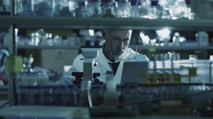 Tired senior male scientist is working with a microscope in a laboratory - stock footage