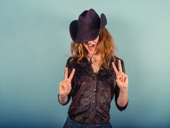 Woman wearing cowboy hat showing peace sign - stock photo