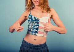 Woman in stars and stripes with thubs up - stock photo
