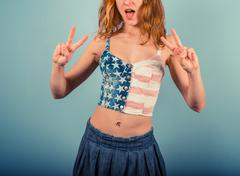Woman in stars and stripes showing peace sign - stock photo
