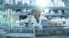 Senior male scientist is concentrated while working with a microscope in a lab - stock footage
