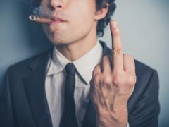 Young businessman with cigar showing rude gesture - stock photo