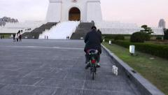 Man wheel bicycle, small dog run beside, POV camera follow behind Stock Footage