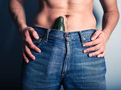 Man with cucumber down his pants - stock photo