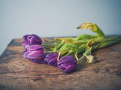 Dead flowers on wooden table - stock photo