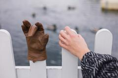 Hand holding fence with glove - stock photo