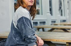 Young woman sitting on bench outside pub - stock photo