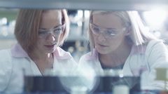 Two female scientists are working with  liquid samples in a tube in a laboratory Stock Footage