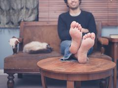 Young barefoot man resting on sofa at home - stock photo