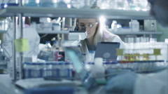 Female scientist is using a microscope and a tablet while working in a lab Stock Footage