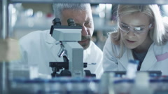 Male and female scientist are working with a microscope and a tablet in a lab - stock footage