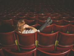 Stock Photo of Woman talking on phone in auditorium