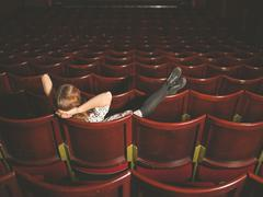 Young woman sitting in auditorium - stock photo