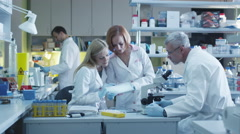 Stock Video Footage of Team of caucasian scientists in white coats are working in a modern laboratory