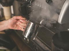 Hand placing metal cup under coffee machine tap - stock photo