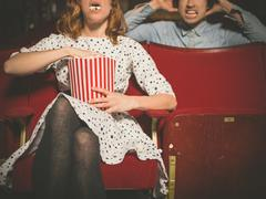 Woman annoying man in cinema by eating popcorn - stock photo