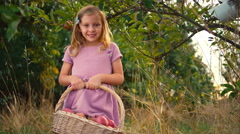 A cute young girl next to a tree holding a basket of apples Stock Footage