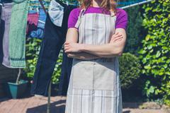 Woman in apron standing by clothes line Stock Photos