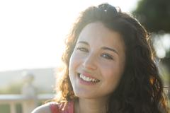 Portrait of an attractive woman smiling to camera with sunlight behind her Stock Photos