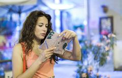 Attractive woman looking at a map at night in a street Stock Photos