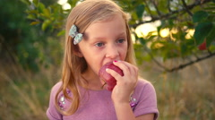 A cute little girl takes a bite out of a fresh apple Stock Footage