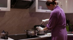Stock Video Footage of A woman stirs a pot spoon adds seasoning