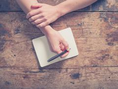 Woman writing in notepad at wooden table Stock Photos