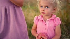 A cute little girl in a field holding an apple Stock Footage