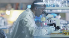 Male scientist is working on a microscope in a laboratory - stock footage