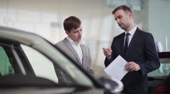 Salesman explains the customer car specifications - stock footage