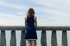 Young woman admiring sea from promenade - stock photo