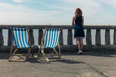 Woman admiring the sea from promenade with deck chairs - stock photo