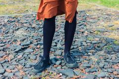 Feet and legs of young woman standing on gravel - stock photo