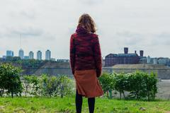 Young woman standing on grass and admiring the city - stock photo