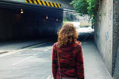 Woman walking on the street near an underpass - stock photo