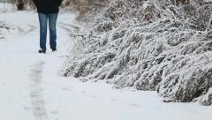 Man walking along snowy winter road Stock Footage